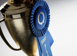 Gold trophy with blue first place ribbon attached to trophy